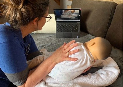 Therapist working with baby doll in front of laptop screen