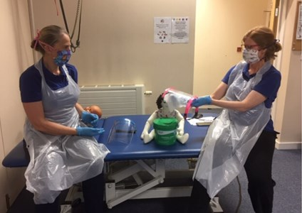 two therapists with visors, gloves and aprons