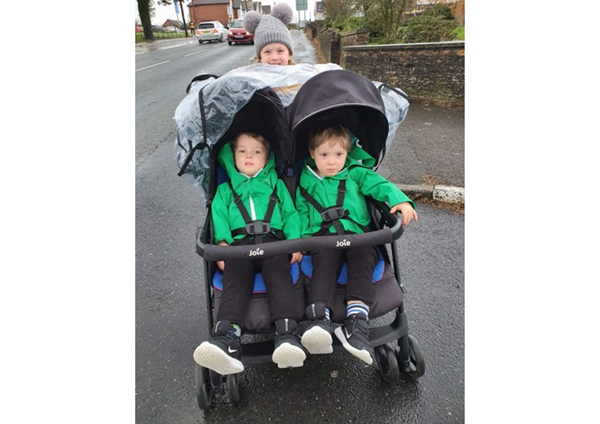 twin boys in push chair with older sister