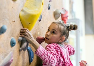 young girl using a climbing wall